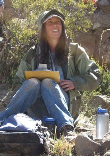 Tiffiny Tung is wearing jeans, a green jacket with the hood up, and a white baseball cap. She has long brown hair. She is in the field- sitting on the ground by rocks, shrubs, and water bottles. She is holding a clipboard and smiling to the right of the camera.
