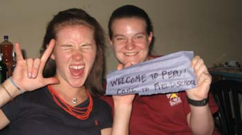 "Cat and Samantha smiling into the camera. Samantha is holding up a piece of duct tape that says ""Welcome to Peru! Come to field school."" Cat (left) is holding up a ""I love you""/""rock"" sign with her hand. She is wearing a black shirt and a red necklace. She has brown hair. Samantha is wearing a red shirt."