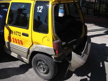 A yellow SUV with it's bumper coming off. The trunk is open. There are black and red numbers on the side door.