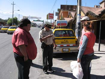 A yellow SUV with numbers on the back. There are three people and a police officer are standing on the sidewalk. The person on the left is wearing a red shirt and black pants. They have black hair. The office is wearing a khaki shirt, black pants, and a khaki hat. They are looking at something in their hand. You can see the head of the person wearing a white baseball cap. He has a red-ish shirt. The person on the right is wearing a red t shirt, a long gray sleeved shirt, and black pants. They are holding white plastic bags. Their brown hair is in a ponytail.