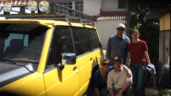 Four people are posing by a plain yellow SUV with a black overhead rack with lights on it. The person in the back left is wearing a blue shirt and a white baseball cap. The person in the back left is wearing a red shirt and their brown hair is in a ponytail. The person on the front left is wearing a blue shirt and sunglasses. The person in the front right is wearing a long sleeved white shirt.