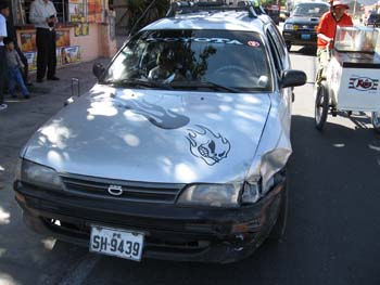 A silver car with two flame decals on the hood. The first is solid black. The second has a face. The right headlight is extremely dented.