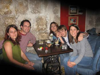 Melihat, Steve, Daniell, Parker, and Tiffiny sitting at a wooden table covered in drinks. On the left side of the table in the front, Melihat is wearing a green sleeveless top and jeans. She has shoulder length brown hair. Steve is wearing a red and white stripped shirt, jeans, and glasses. He has short brown hair. On the other side of the table in the back, Daniell is wearing a blue shirt and has long brown hair. Parker is wearing a gray jacket and jeans. He has short brown hair and a beard. Tiffiny is wearing a gray long sleeved shirt and jeans. She has shoulder length brown hair.