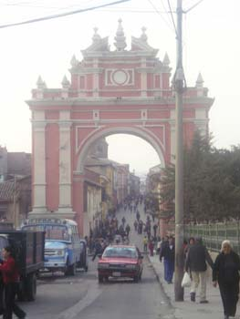 A red and white arch over a street. There are three cars- blue, red, and black- and a lot of people in the street.