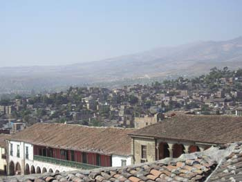 There is a roof made up of rounded ceramic pieces inthe foreground. There are two buildings behind that. The one on the left is white with a brown roof and arches. The other is slightly taller and is made of stone. It also has arches. Behidn those buildings are dozens of building varying in size and color. There are also trees. There are hills in the background.