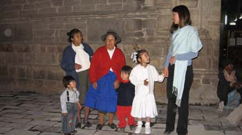 Stephanie, four of her loved ones, and her godmother- Tiffiny. On the left a kid is wearing a gray shirt, black pants, and black suspenders. They have black hair. Next to them, is an adult with a white shirt, blue jacket, and green pants. They have black hair in a bun. Next to them, is a person with a white shirt, red jacket, blue skirt, and a gray hat. Next, is a child wearing a black shirt with a red collar and red pants. They have black hair. Next, is Stephanie wearing all white- jacket, skirt, shoes, and flowers in her hair. On the right is Tiffiny wearing a blue shirt, a light blue scarf around her torso, and black pants. She is holding Stephanie's hand.