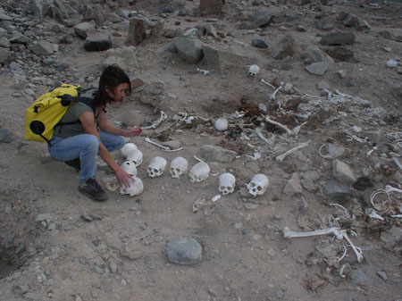 Tiffiny is wearing jeans and a green t-shirt. Her brown hair is shoulder length. crouching by several skulls and other bones that have been looted from their graves.