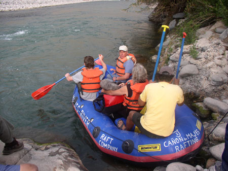 Four people are on a raft right on the shore of a river and are about to paddle off.