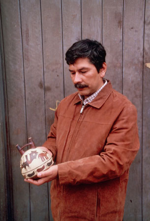 A man in a brown jacket holding a ceramic object with paintings on it.
