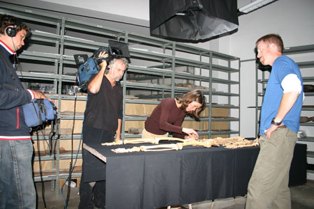 Tiffiny is hunched over a skeleton. Ken, Peter, and AJ are standing around the table. Ken is wearing a blue t-shirt, long sleeved white shirt, and khaki pants. AJ (on the left) is wearing jeans and a blue jacket with white and red on the bottom, collar, and sleeves. He is holding a camera in a blue bag. Peter is wearing a black sweater and dark jeans. His camera is over his shoulder.