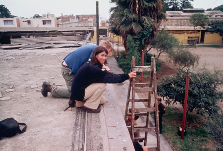 Tiffiny and Ken on a roof sitting by a ladder. It is about a story high and you can see other people clearly on the ground. Tiffiny is wearing a blue jacket and khaki pants. She is looking into the camera. Ken is wearing a blue shirt and khakis and is looking down.