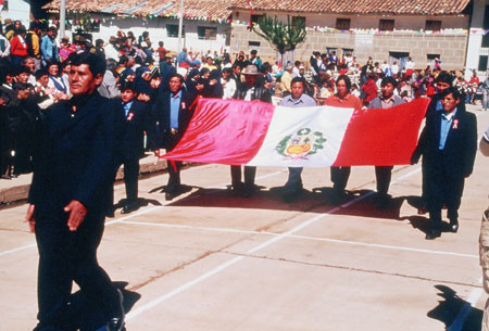 There is a parade of people in the street and people crowding the side walks. In the second in line in the parade is six men holding the Peru flag. It has red on the left and right thirds, and the middle is white with a shieldlike symbol. It has an alpaca, a tree, and a cornocopia in the shield. There is leaves surronding the shield in a almost fully closed circle.