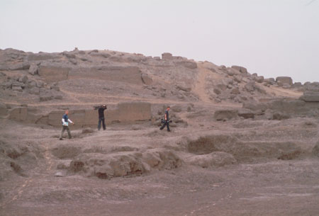 Three in the middle ground of a rocky desert. One of them is Ken in a blue shirt. He is holding papers. The other two men are holding cameras. One is wearing a brown shirt and jeans. The other has a gray shirt and jeans. Those two are holding cameras.