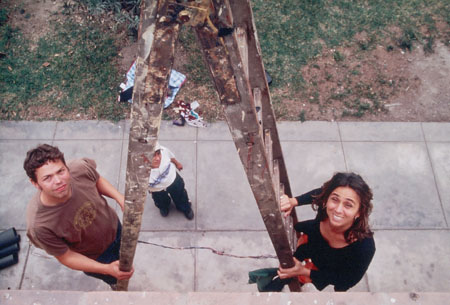 Two people are on each side of a ladder- AJ is on the left and Deb is on the right. There is another person below the ladder. Aj is wearing a brown tshirt with a yellow symbol on it and jeans. Deb is wearing all black. The person on the ground has on a white shirt, white hat, and jeans.