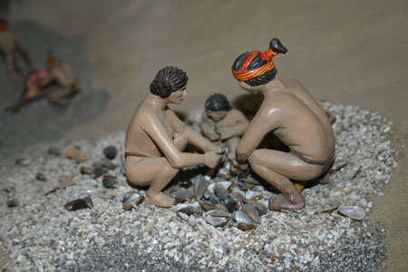 Three small plastic figures are squatting on pebbles and are surrounding a pile of shells.