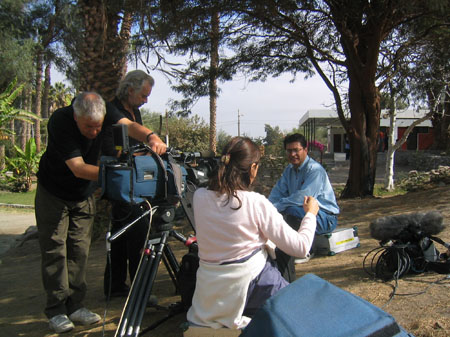 James M is sitting on a briefcase in front of a camera. He is wearing a blue button up, jeans, and glasses. The person with the purple jacket and long brown hair has taken the jacket off. Their shirt is pink. Two people are working on the camera. One is wearing a black shirt and khakis and the other is wearing all black. They both have gray hair.