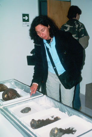 Kate has black curly hair. She is wearing a sweatshirt and a black jacket. She has a black bag over her shoulder. She is pointing at a skull in a white tray. There is another skull and three other mumified parts on the table. Kelda is a wearing a camo shirt with short brown hair in the background. She is not facing the camera.