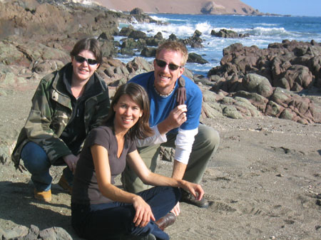 Kelda, Tiffiny, and Ken are sitting on a rocky beach. They are all looking into the camera and smiling. There is waves in the water behind them. Kelda (the left) is wearing a camo jacket, jeans, and sunglasses. Her hair is short and brown. Tiffiny is wearing a purple t-shirt and jeans. Ken is wearing a blue tshirt, white long sleeved shirt, khakis, and sunglasses. He is holding a figure in the shape of a person.