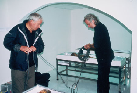 Les and Peter are unwinding a cord. Les (on the left) is wearing black shirt, black jacket, and gray pants. Peter is wearing all black. Both of their hair is gray.