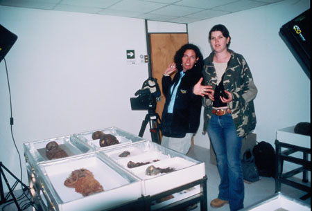 Kate and Kelda are stanind by mummified skulls, children, and other parts on a table. There is a camera pointing at the table. They are both looking into the camera. Kate (on the left) is waving. She has black curly hair. She is wearing a sweatshirt and a black jacket. She has a black bag over her shoulder. She is pointing at a skull in a white tray. There is another skull and three other mumified parts on the table. Kelda is a wearing a camo shirt with short brown hair in the background.