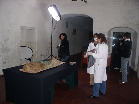 There is a mummy on a black table with a light shining on it. There is a person stanidn by it with a camera. There are two people wearing lab coats and masks. There are three people in the smaller doorway with masks on as well.
