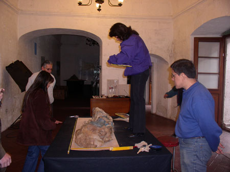 A mummy is laying on a black table. A person is standing on the table in a bright purple jacket with dark brown hair. On the same side of the table (right) there is someone wearing a blue shirt and jeans. on the other side of the table there is someone with long brown hair and a red jacket. There is someone in the background in a white shirt, gray hair, and sunglasses on.