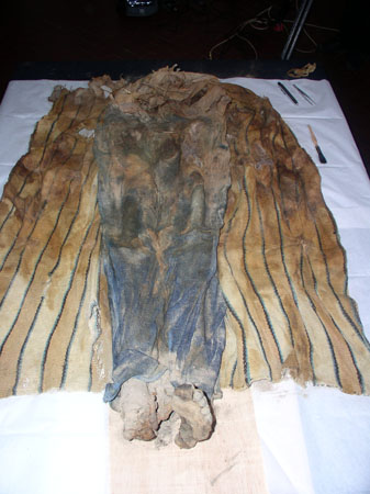 The legs of a mummy have been unwrapped. They appear to have been wearing jeans when they died. Their feet are bare but still have skin on them. They were wrapped in a blanket of some kind- which is under them.