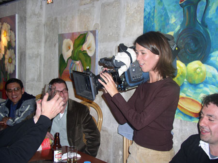 Tiffiny is holding a camera on her shoulder. She is wearing a red shirt and khakis. She is filming a glass that someone is holding. There are three other people sitting on her side of the table. There are paintings on the wall behind her. One of a pitcher and fruit, one of white avocado shaped flowers in a vase, and one of white daises in a vase.