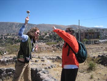 Cat and Ellen demonstrating how a person might get a parry fracture. Cat is holding an object above her head, acting like she's going to swing it down at Ellen. Ellen is holding her arm up to protect her face. There are hills covered in rocks and cacti in the background. There is a brown building in the distance. Cat is wearing a light and dark blue striped shirt, sunglasses, a green vest, and khaki pants. Her brown hair is at her shoulders. Ellen is wearinga red jacket, whire shirt, black pants, sunglasses, and a black backpack over her shoulder.