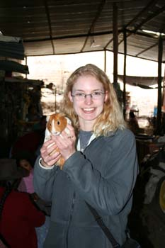 KC- wearing a gray jacket and glasses- is holding a brown and white guinea pig. She is smiling into the camera. Seh has blonde curly hair down to her shoulders.