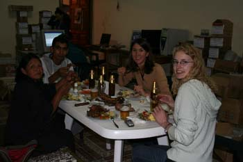 Gloria (left), a person, Tiffiny, and KC are sitting at a white table eating dinner. The only lighting is the camera flash in a dark room. They are all looking into the camera. Gloria is wearing a dark color. She has shoulder length black hair. The person next to her is wearing a white shirt. Tiffiny is wearing a brown shit and has shoulder length dark brown hair. KC is wearing a white jacket and glasses. She has blonde curly hair. There is bottles and food on the table.