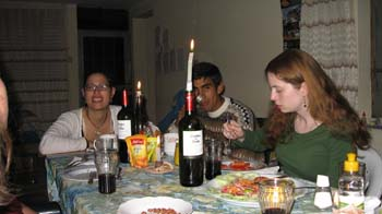 Danielle, Jimmy, and Allison sitting a table eating. Danielle is wearing a white shirt as well as glasses and smiling into the camera. Her hair is in a brown ponytail. Jimmy's face is behind the candle in the wine bottle. He is wearing a brown, black, and white sweater. He has black hair and is looking into the camera. Allison is wearing a long-sleeved green shirt. She is looking at her plate. She has long brown hair.