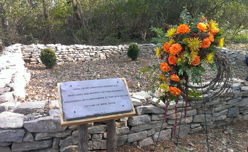 "There is a small rectangular stone wall with headstones inside the barrier. There is a plaque that says ""Here lies 20 unknown individuals who lived and worked on this property, reinterred with reverence at this site on the 12th day of June, 2014"" next to a wreath with orange and yellow flowers."