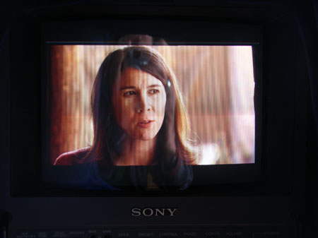 "A black screen with ""Sony"" written on the bottom in white letters. Tiffiniy is in the frame. She is looking into the distance. The reflection of the person taking the photo can be vaguely seen."