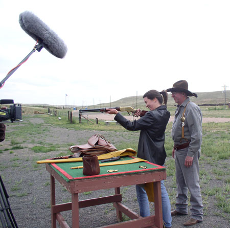 Tiffiny is holding a rifle. She is wearing a black jacket, jeans, and her hair is in a pony tail. Bill is standing behind her in a gray shirt, jeans, a brown cowboy hat, and badges pinned on his orange suspenders. There is a boom mic in the corner of the shot.