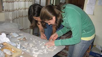 Tiffiny and Cat are hunched over a gray table with white ceramic shards on it. Tiffiny is behind Cat. You can see that she is wearing jeans. She has dark brown shoulder length hair. Cat is wearing a light yellow shirt, teal jacket, and jeans. She has shoulder length brown hair.