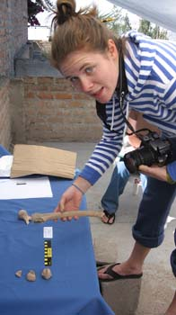 Cat is standing next to a brick wall and in front of a table with a blue table cloth. She is holding a bone in her hand and their are fragments on the table. There is a yellow and black ruler on the table too. She has a camera around her neck and looking into the camera taking the photo. She is wearing a white and blue striped jacket, jeans, and black flip flops. Her brown hair is in a bun.
