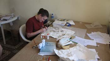 Samantha is gluing fragments together. The table is brown and is covered in paper, books, and things to wrap bones in. She is wearing a red shirt and her brown hair is in a pony tail.