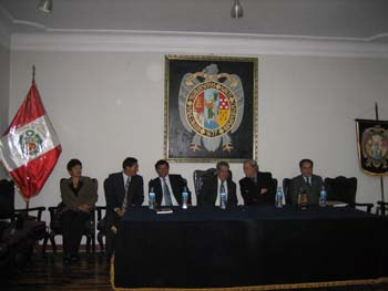 Six people wearing suits sitting at a table with a black table cloth in a dark room. They are sitting in wooden chairs in a short wooden stage. There is a large seal behind them on the wall. This seal is on a flag on the right. On the left, is the Peruvian flag.