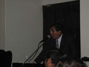 Jose Ochatoma is standing at a podium and speaking into a microphone. He is wearing a dark colored suit, glasses, and a yellow and gray striped tie. He has short black hair. You can see the top of two heads with dark in the foreground. The room is dark.