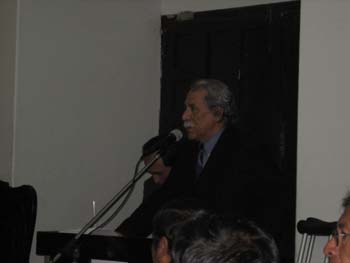 Luis Lumbreras is standing at a podium with a microphone. He is wearing a dark blazer and a blue collared shirt. He has gray hair and mustache. You can see the top of two heads with dark hair and part of a face in the foreground. The room is dark.