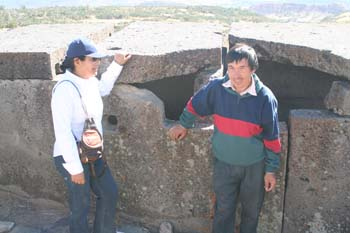 Someone and Lorenzo are leaning against large flat stones. The person on the right is wearing a white shirt, jeans, sunglasses, and a navy baseball cap. They have a brown bag across their shoulder and black hair in a bun. Lorenzo is wearing a jacket that is blue on top, green on the bottom, and a red stripe between the two. They are wearing gray pants. They have short black hair and a beard.