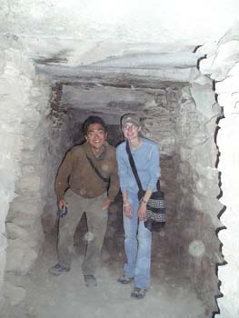 A person and KC are standing in an underground stone tunnel. The person on the right is wearing a brown jacket and gray pants. They have short brown hair. KC is wearing a blue shirt, jeans, glasses, and a green baseball cap. The both have a black bag over their shoulder.