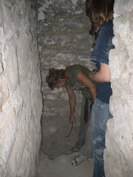 Amy and Emily are in an underground tunnel made of stones. The ground is rock. Amy(?) is pointing at something on the ground with a metal tool.The person on the left (Amy?) is wearing a green tshirt and brown pants. Her brown hair is in a ponytail. Emily is wearing a blue tshirt and jeans. She has shoulder length brown hair.