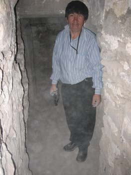 Lorenzo is in an underground tunnel made of stones. The ground is rock. Lorenzo is wearing a blue and white striped shirt and black pants. He has short lack hair.