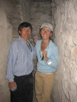 Lorenzo and Tiffiny are in an underground tunnel made of stones. Lorenzo is wearing a blue and white striped shirt and black pants. He has short lack hair. Tiffiny is wearing a bleu jacket, khkai pants, and a white baseball cap. She is holding a a flashlight.