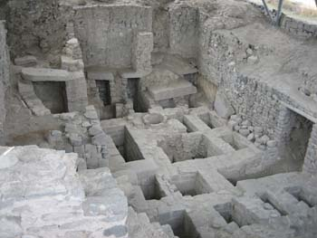 There is a large hole in the ground with stone architecture. On the ground, there are rectangular and square holes in the ground. They are divided by stone paths. There are small and large holes and arches in the walls. The walls are made of stones.