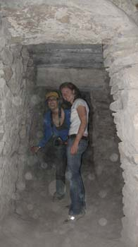 Danielle and Cat in an underground tunnel. They are crouching down. Danielle is wearing a blue shirt, jeans, and a yellow baseball cap. She has a camera around her neck. Cat is wearing a white shirt and jeans. She has shoulder length brown hair. They both smiling into the camera.