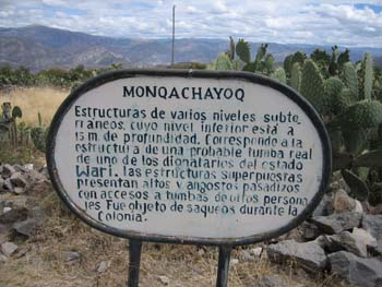 "A sign in the ground. There is grass, rocks, and cacti on the ground. There is a mountain in the distance. The sign is black and white. It reads ""Monqchayoq- Estructuras de varios niveles subte-rraneos cuyo nivel inferior esia a ism de profundidad. Corresponde a la estructura de une probable tuniba real de une de los dionatarius del estado Wari. Las estrucicturas superpuesias presentan altos vangostos pasadios con accesos a tumbas de deuitos personas jes Fue objecto de saqueos durante la Colonia."""