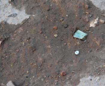 There is a brown patch of dirt and there is gray on all side. In the dirt, there is rocks and a rectangular piece of turquoise in the dirt.